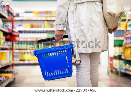 Pretty young woman buying groceries in a supermarket/mall/grocery store (color toned image; shallow DOF) - stock photo