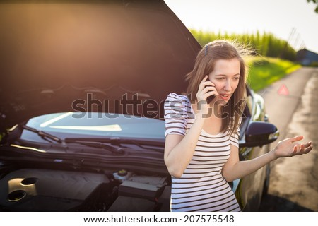 Pretty, young woman calling the roadside service/assistance after her car has broken down - stock photo
