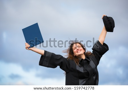 Pretty, young woman celebrating joyfully her graduation - spreading wide her arms, holding her diploma, savouring her success