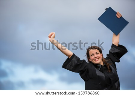 Pretty, young woman celebrating joyfully her graduation - spreading wide her arms, holding her diploma, savoring her success (color toned image; shallow DOF) - stock photo