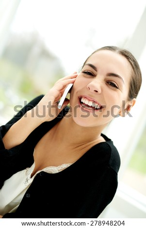 Pretty young woman chatting on her mobile phone smiling with pleasure as she listens to the conversation, high key window background - stock photo