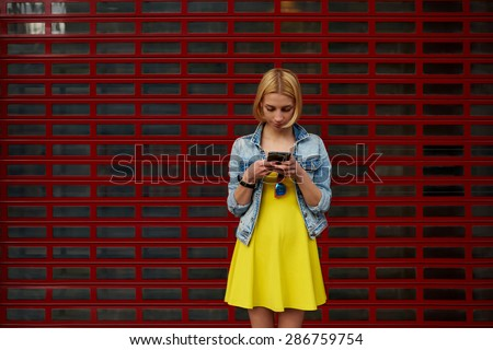 Pretty young woman chatting on smart phone against blank copy space bright background for your content or text message, female hipster student in the dress using mobile phone for connect to wireless - stock photo