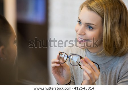 Pretty, young woman choosing new glasses frames - stock photo