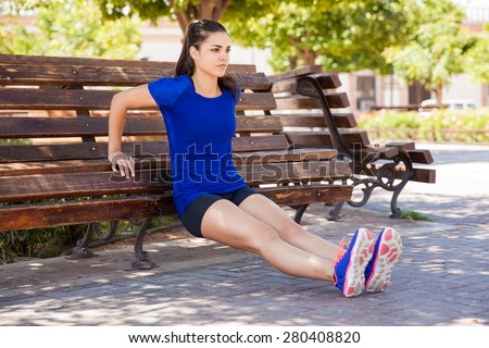 Pretty young woman concentrating on her workout, leaning on a park bench - stock photo