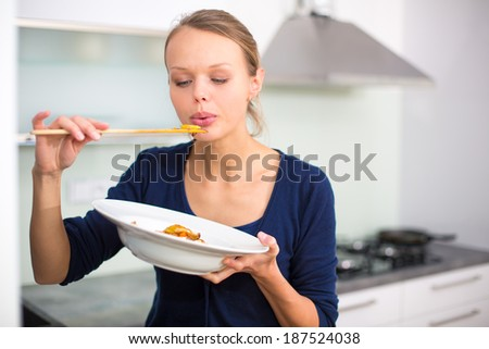 Pretty, young woman cooking a diner in a modern kitchen, tasing the food she made - stock photo