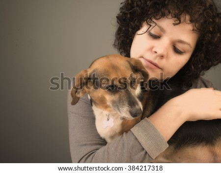 Pretty young woman cuddles affectionately with beagle dog - stock photo