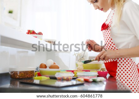 pretty young woman decorating cupcakes on her kitchen portrait of a beautiful female business owner