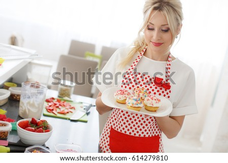 Woman Decorating Cupcakes woman baking home happy woman baking stock photo 447897559