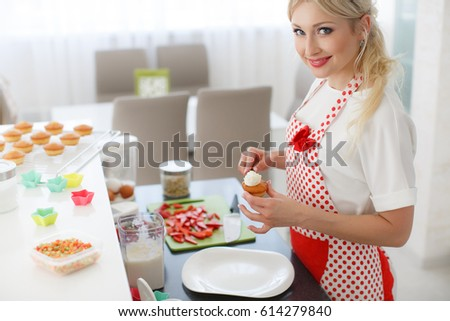 pretty young woman decorating cupcakes on her kitchen portrait of a beautiful female business owner - Woman Decorating Cupcakes