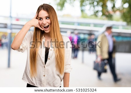 pretty young woman doing calling gesture