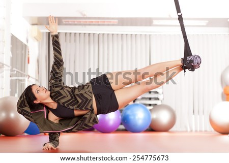 pretty young woman doing exercises with a hanging band