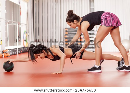 pretty young woman doing exercises with a medicine ball and instructor