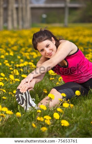 Pretty young woman doing stretch exercises in a field of dandelions - stock photo