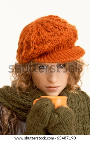 Pretty young woman dressed up warm, drinking hot tea, freezing.? - stock photo