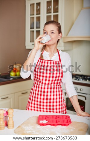 Pretty young woman drinking kefir in the kitchen
