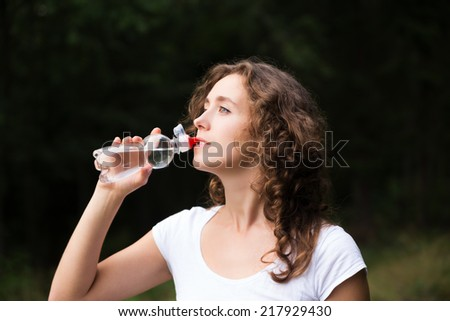 Pretty young woman drinks water