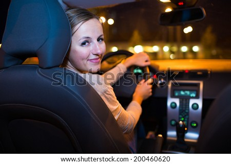 Pretty young woman driving her new car - stock photo