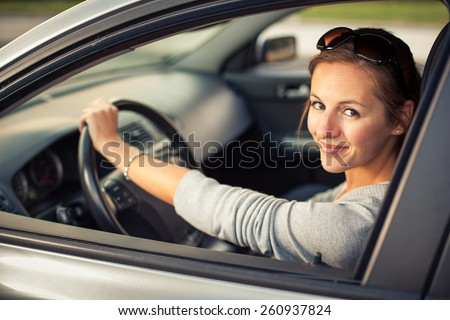 Pretty young woman driving her new car  (color toned image; shallow DOF) - stock photo