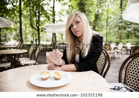Pretty young woman eating in  restaurant - stock photo