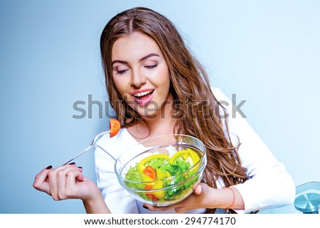 pretty young woman eating salad of vegetables, against blue background - stock photo