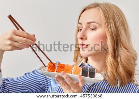 pretty young woman eating sushi looking at camera - stock photo