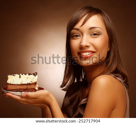 Pretty young woman eats a sweet cake - stock photo