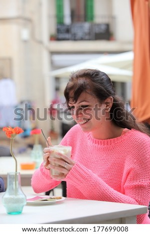 Pretty young woman enjoying a glass of cappuccino as she sits outdoors at a table in an open-air restaurant