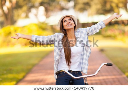 pretty young woman enjoying riding bike at the park with arms outstretched - stock photo