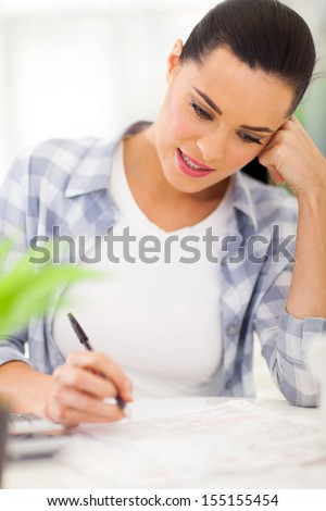 pretty young woman filling her tax forms - stock photo
