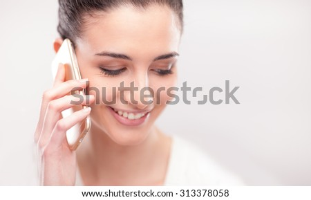Pretty young woman having a phone call with her mobile on white background - stock photo