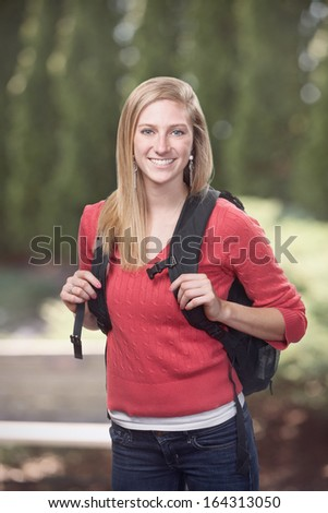 Pretty young woman high school or college student on campus - stock photo