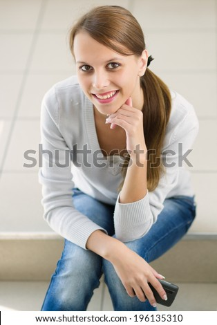 Pretty young woman holding a cell phone