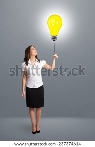Pretty young woman holding a light bulb balloon - stock photo