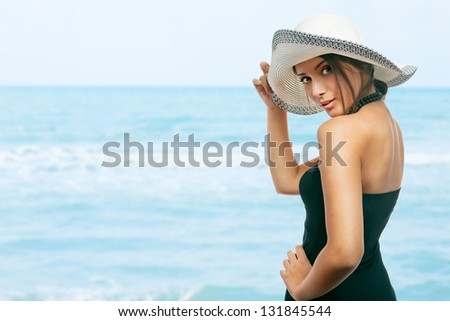 Pretty young woman holding her hat on her head, at the beach - stock photo