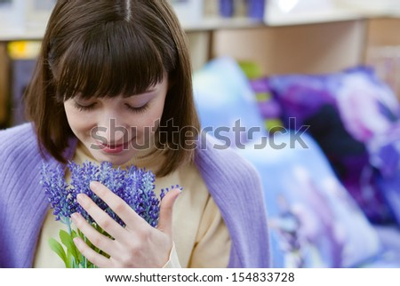 Pretty young woman holding lavender on the indoors background - stock photo