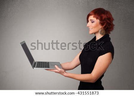 Pretty young woman holding modern laptop