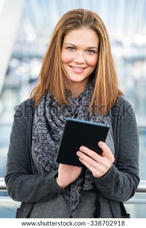pretty young woman holding tablet in hands
