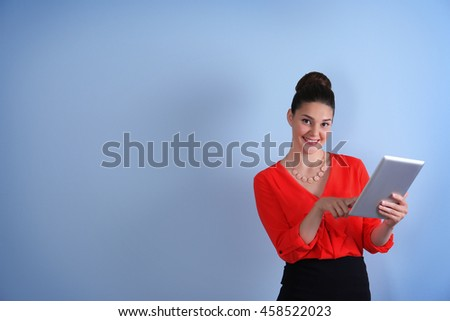 Pretty young woman holding tablet on light background