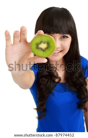 Pretty young woman holds kiwi in front of her eyes. in isolated white background
