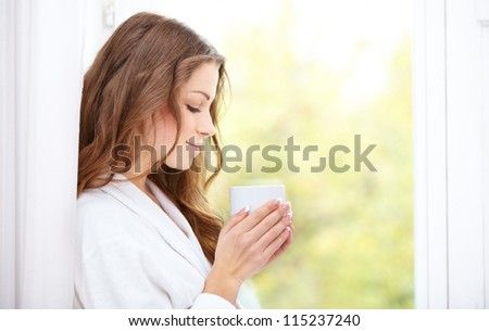 Pretty young woman in a bathrobe enjoying a cup of coffee while looking out of her window - stock photo