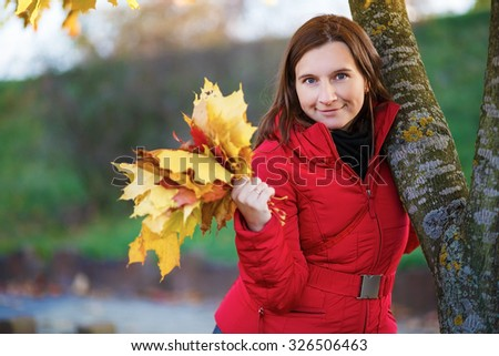 Pretty young woman in a beret and red jacket with autumn yellow maple leaf in his hand. Shallow depth of field. Selective focus on model.