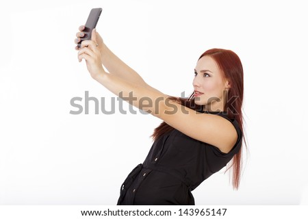 Pretty young woman in a blue dress takes a selfie with her smart phone.