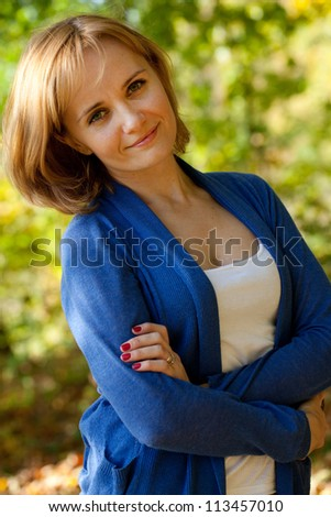 Pretty young woman in a blue knitted pullover - stock photo