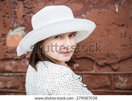 Pretty young woman in a white blouse and hat posing on a background old vintage brown brick wall. Female portrait in a retro style. Selective focus on the model's face. - stock photo