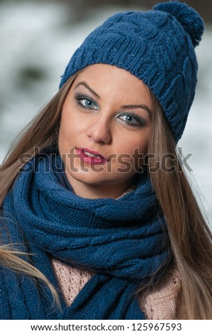 pretty young woman in a winter fashion shot.Winter wild girl on snow.Winter Girl with beautiful make up, and snow flake, forest background.Portrait of attractive girl
