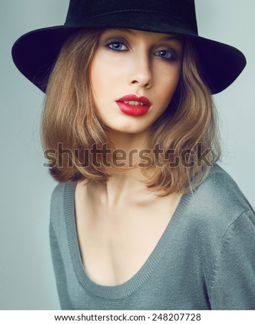 Pretty young woman in black hat with perfect make up. Red lips and blue eyes. - stock photo
