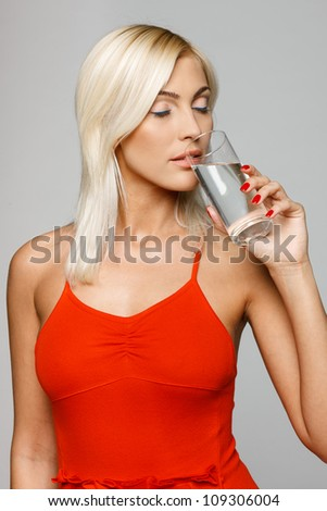 Pretty young woman in bright red dress enjoying fresh water with closed eyes, over gray background - stock photo