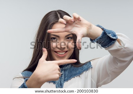Pretty young woman in casual peering through a square form by her hands as a movie director might do isolated on white - stock photo