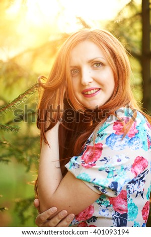 Pretty young woman in dress standing on the background of the forest, touches her hair and looks into the camera