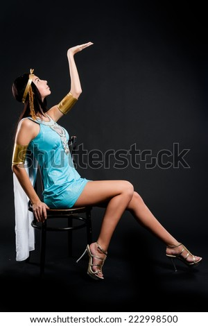 Pretty young woman in egyptian queen costume sits on chair over black background - stock photo
